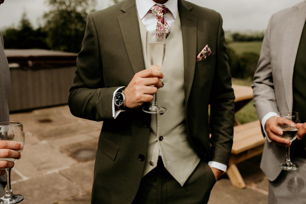 groom holding glass of champagne during groom prep