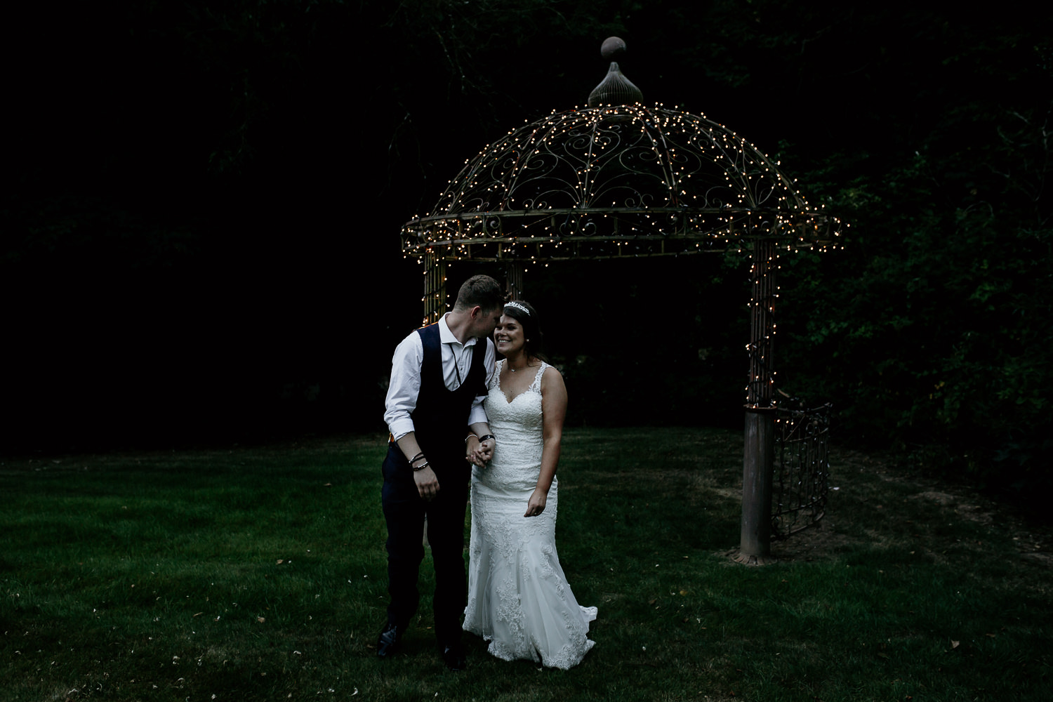 photo of groom looking back at bride outdoors near fairy lights