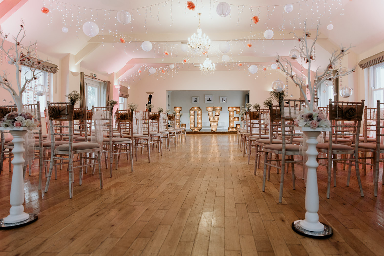 romantic and fun ceremony venue decorated with pink and white vintage chairs fairly lights hanging paper balls and large light up LOVE sign