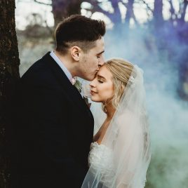 groom kisses brides forehead in smokey wooded area