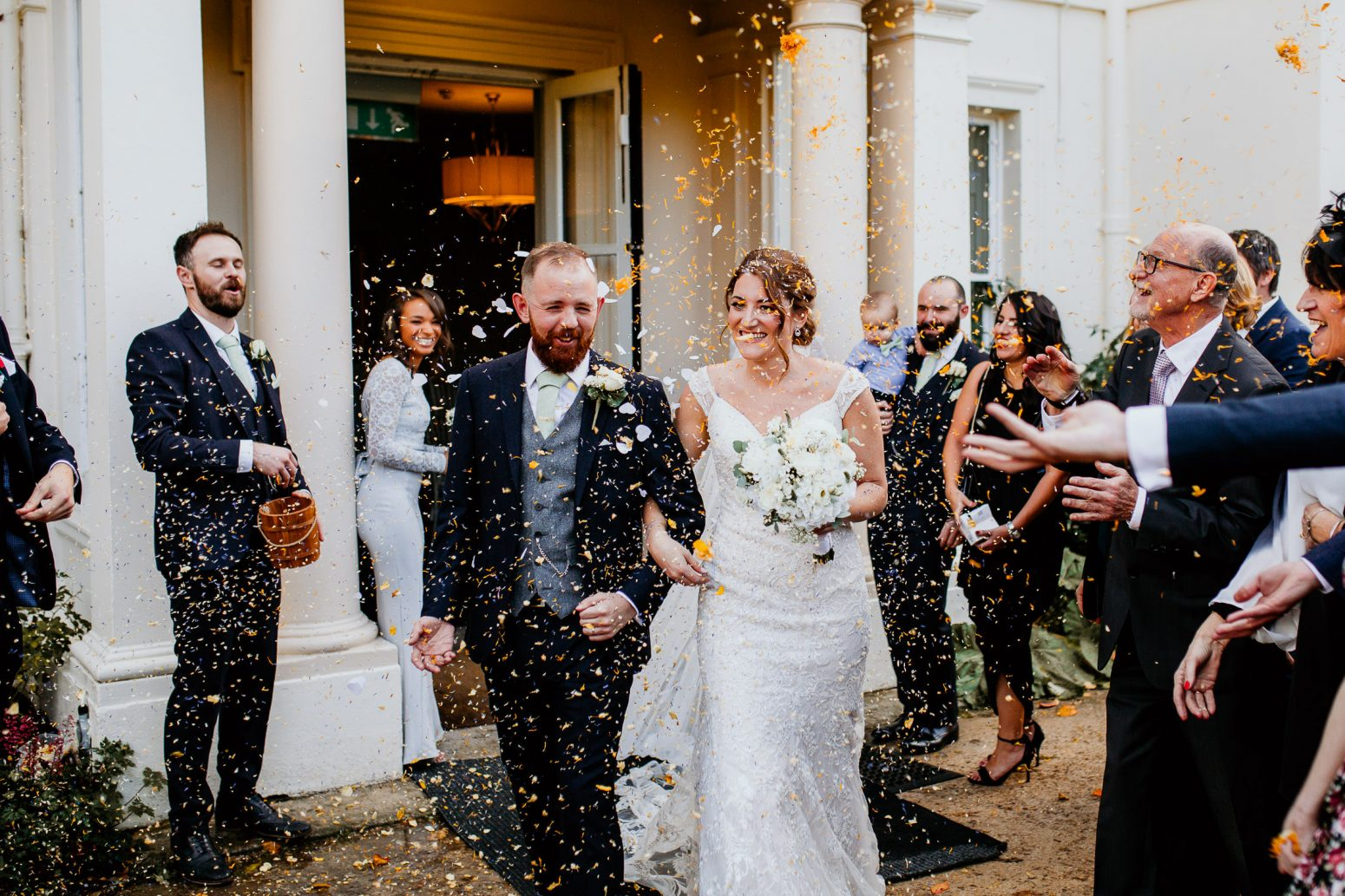 bride in embroidered wedding dress and groom in luxurious suit with green tie and white rose buttonhole walk arm in arm under falling confetti surrounded by smiling wedding guests