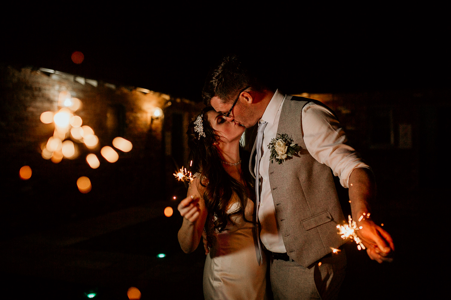 photo of the bride and groom kissing and holding sparklers