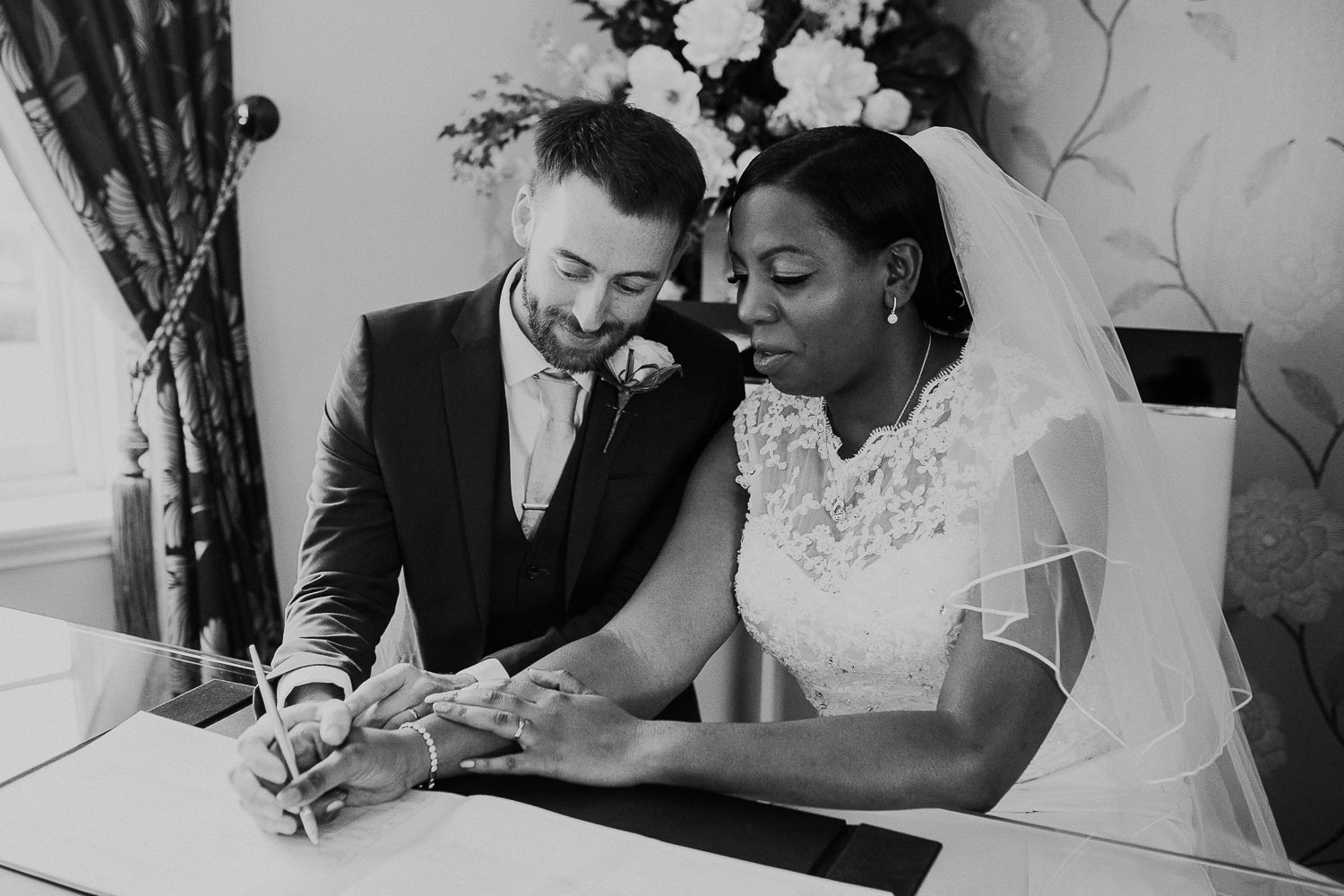 black and white photo of smiling bride and groom sign their wedding register