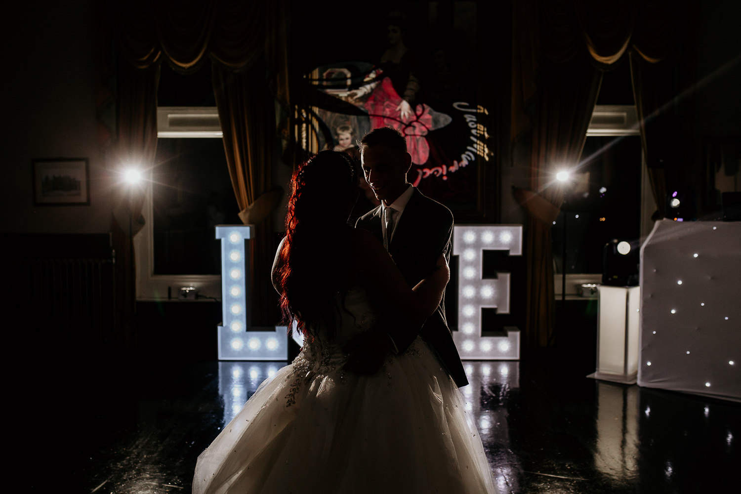 bride and groom in silhouette dancing in front of light up LOVE sign