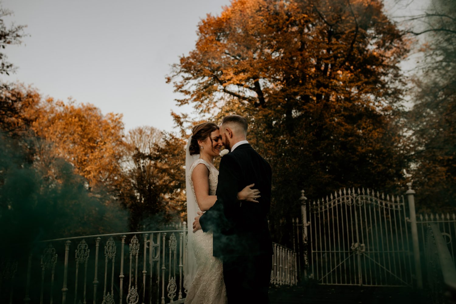 smiling bride and groom embrace in an autumn woodland setting