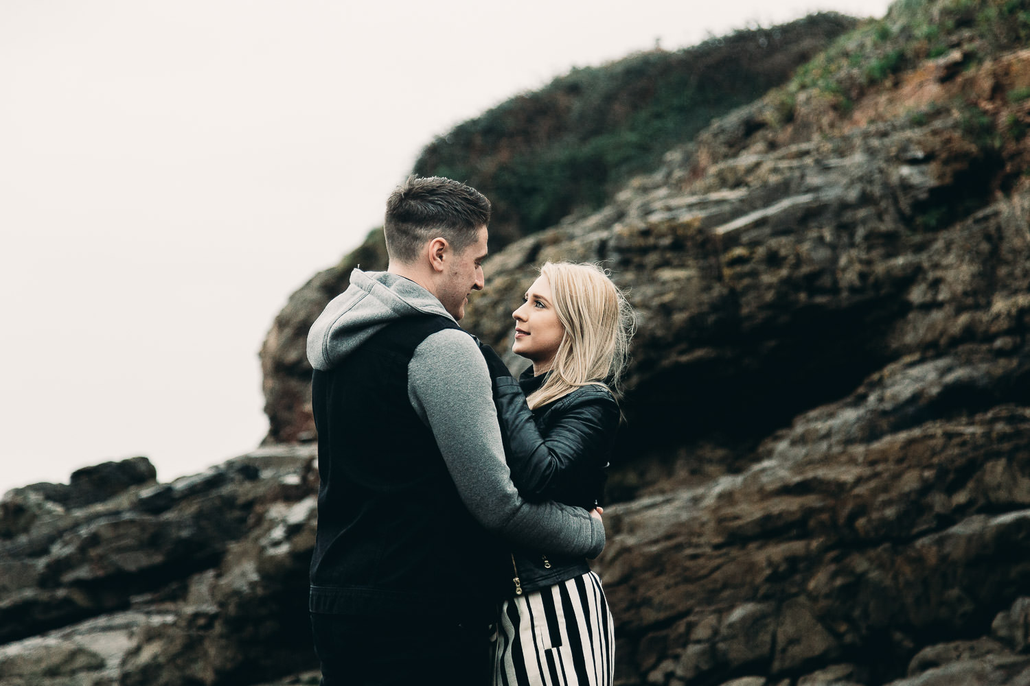 Bide and groom look into each others eyes standing near cliff on seaside engagement shoot