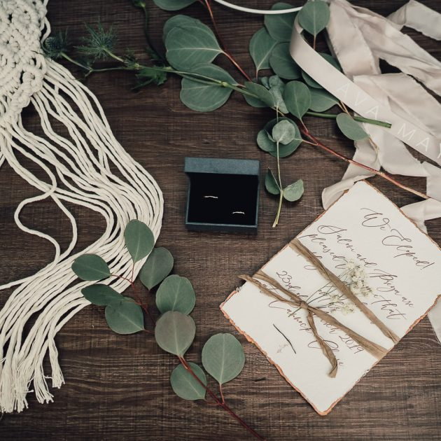 flat lay styled image of wedding rings, wedding invitations and macrame bouquet wraps