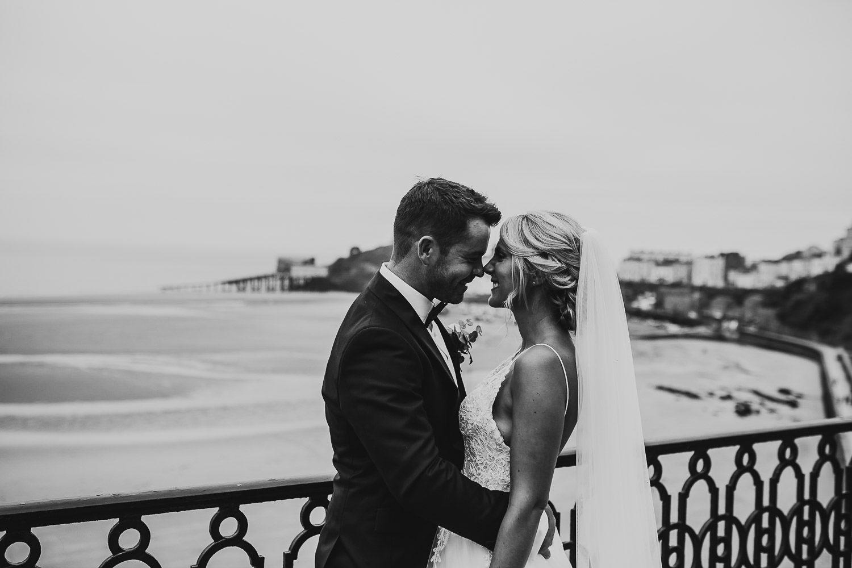 luxury bride and groom cuddling at tenby beach