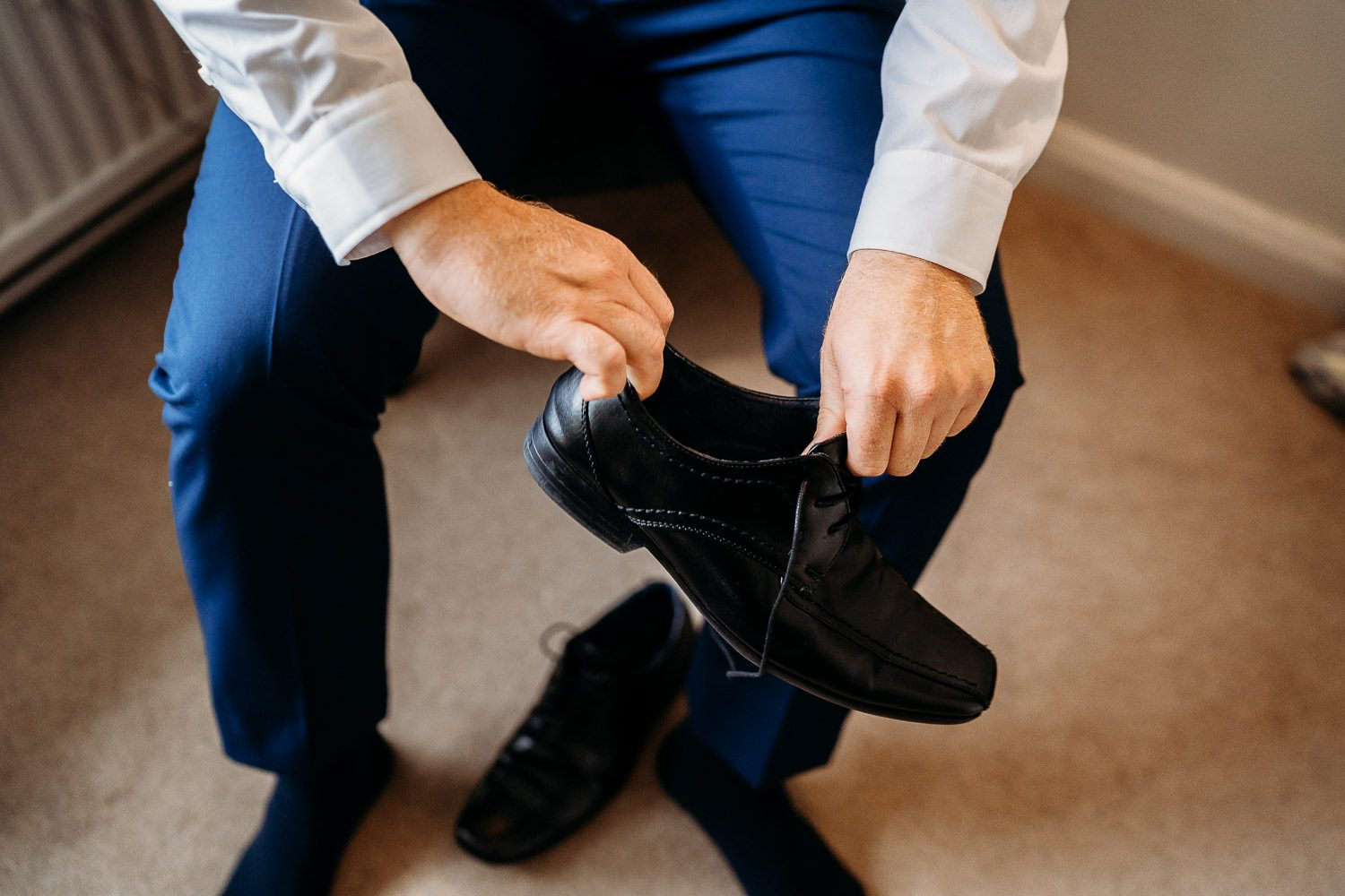 groom putting on shoes during groom preparations