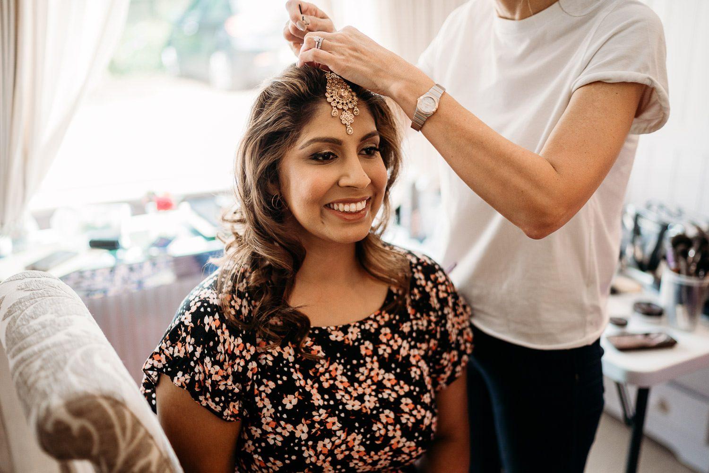hairdresser placing maang tikka on bride's head