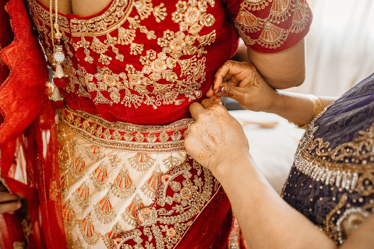 brides mother pinning red sari for bride