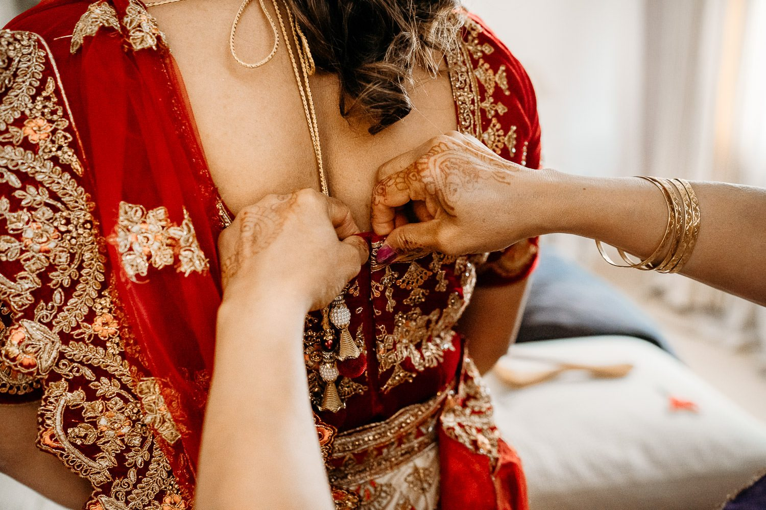 brides mother helping bride put on red sari for wedding