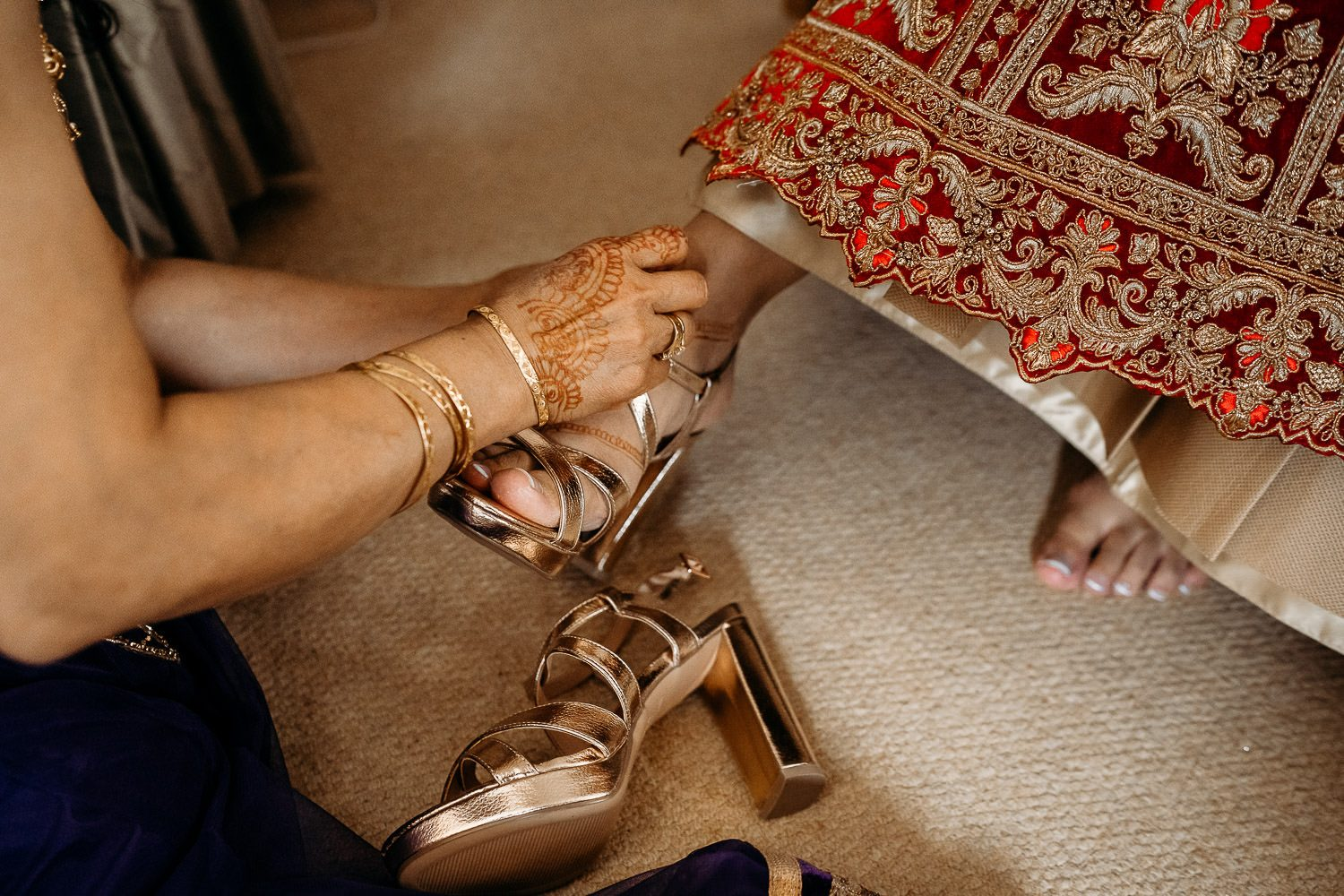 bride in red sari putting on wedding shoes