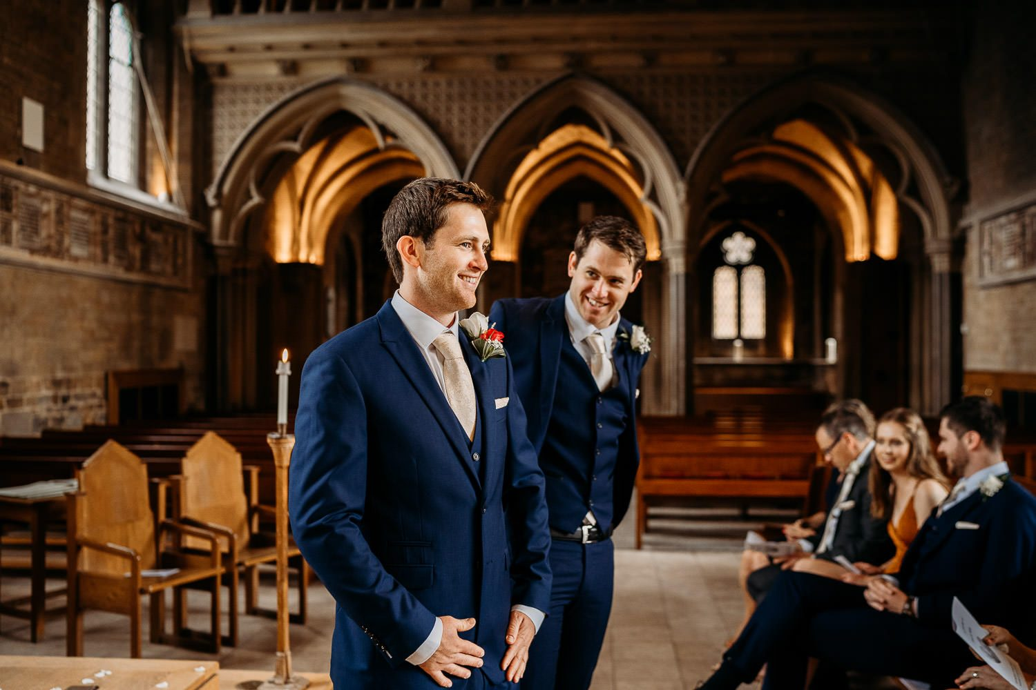 groom and brother smiling while waiting for bride at alter