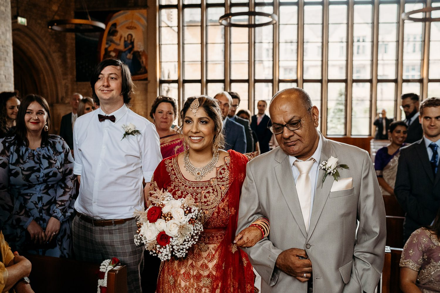 bride in red sari walking down isle with father at uppingham chapel