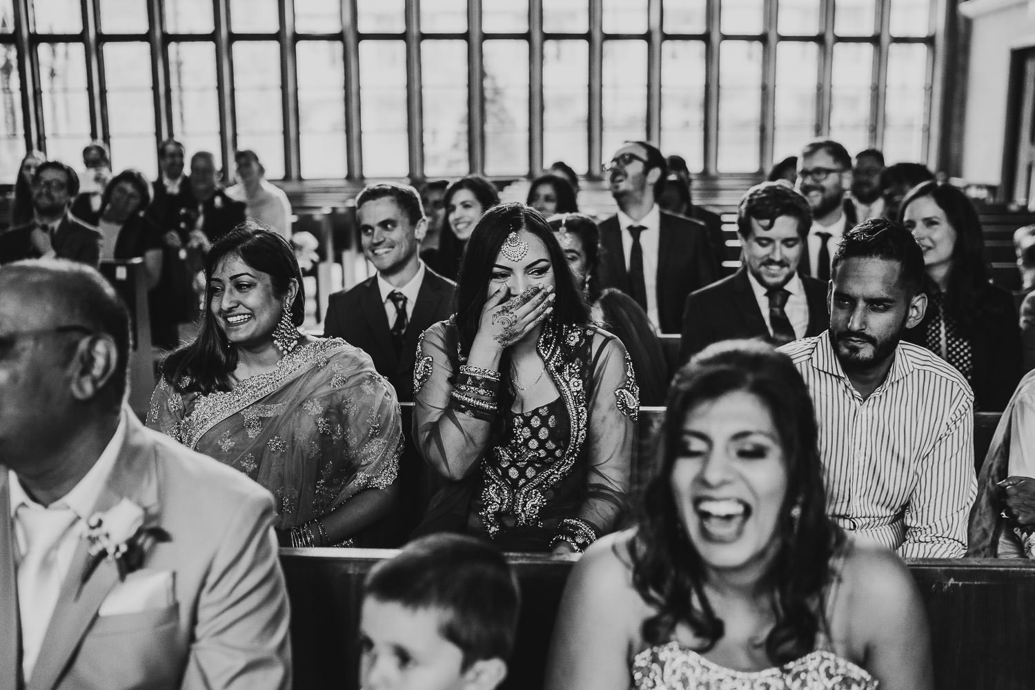 wedding guest laughing during indian wedding ceremony
