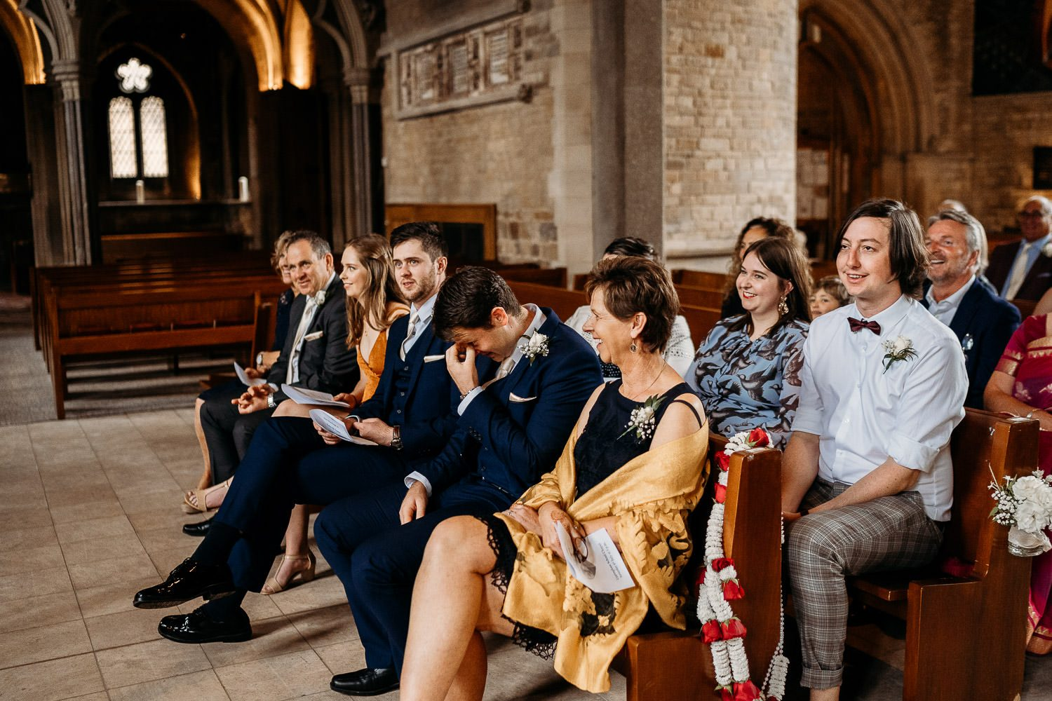 wedding guests laughing during ceremony in uppingham chapel