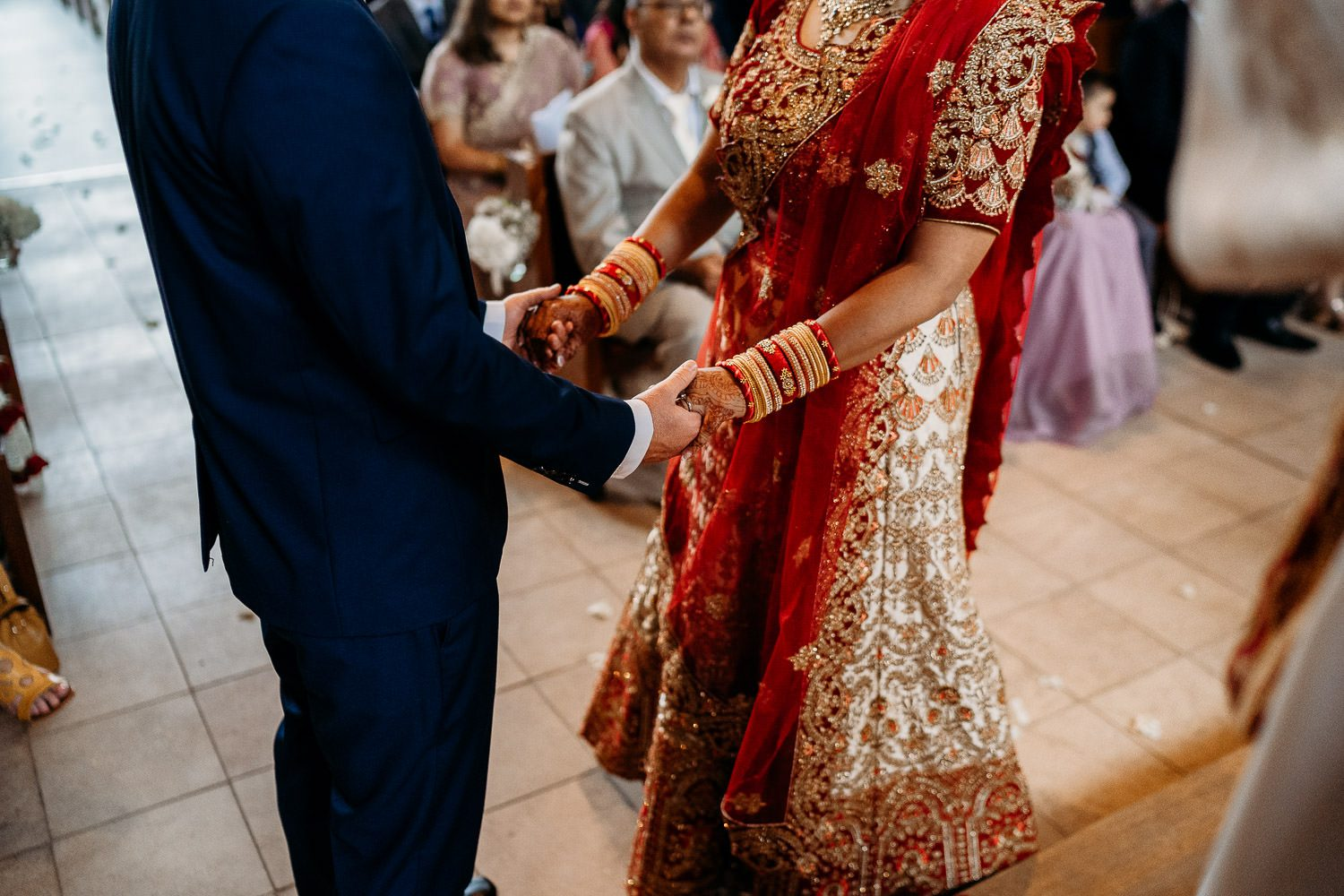 indian bride and groom holding hands during wedding ceremony