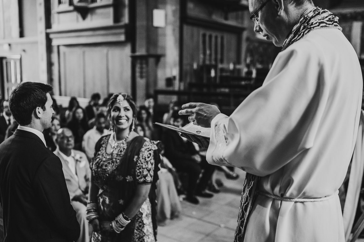 vicar blessing wedding rings during wedding ceremony in uppingham chapel