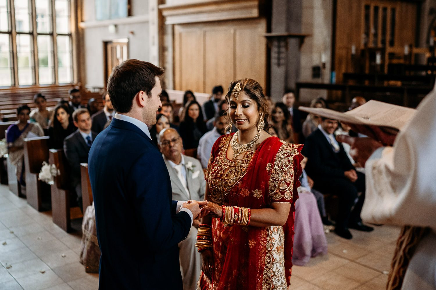 groom placing ring on brides finger during asian wedding