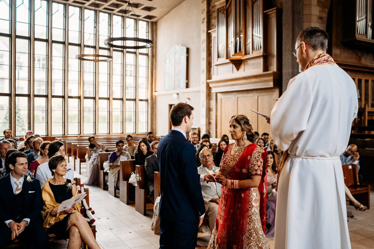 asian bride and groom smiling at each other during wedding ceremony in uppingham chapel