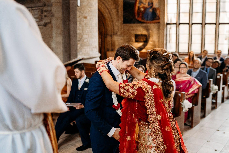 bride placing flower garland during indian wedding ceremony