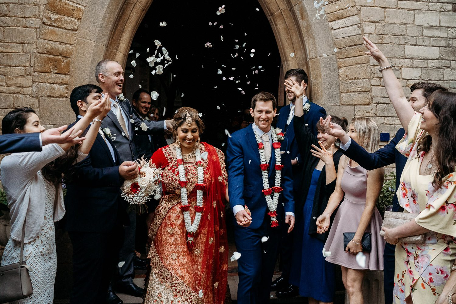 indian bride and groom laughing during confetti throwing