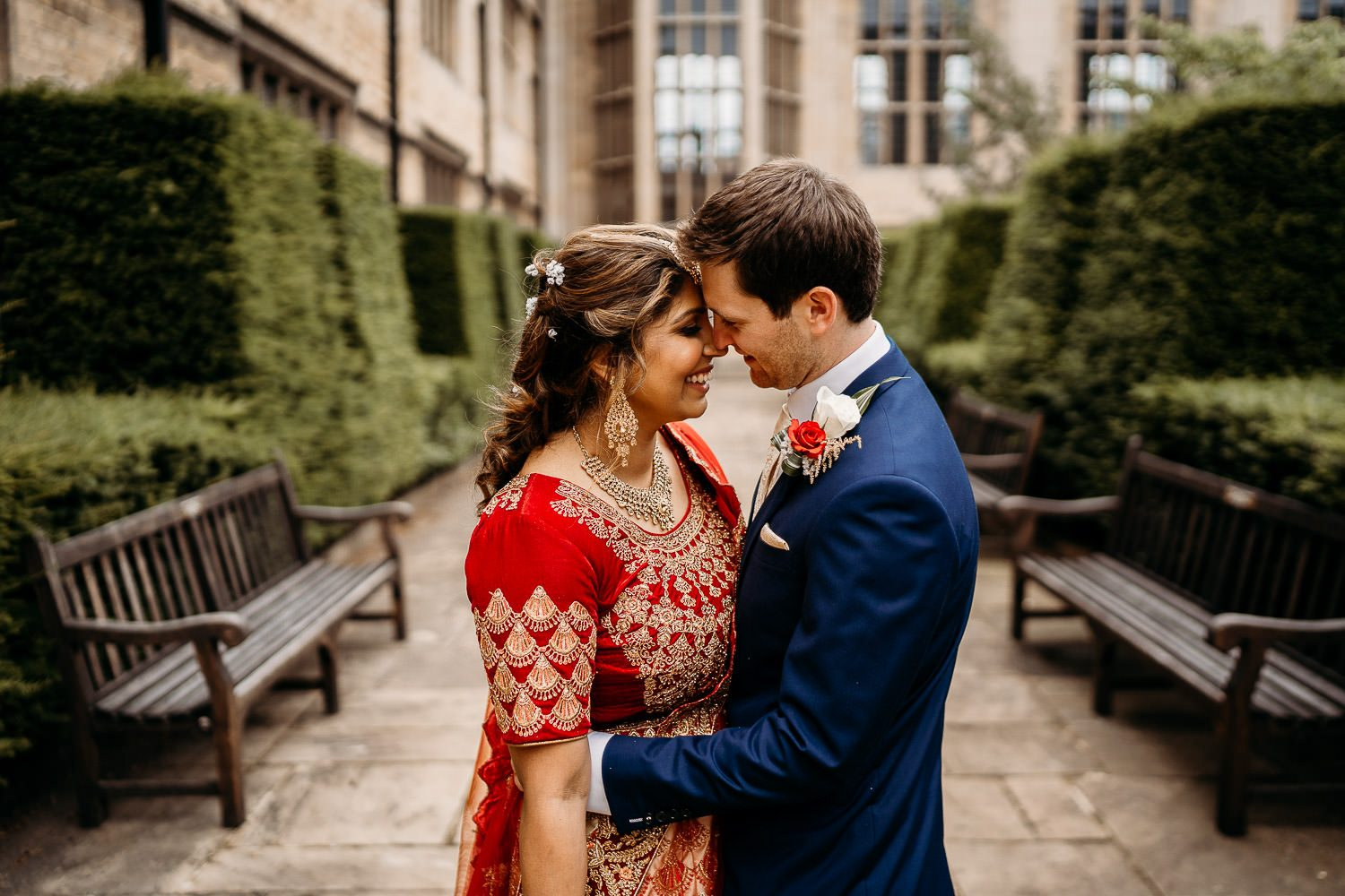 indian bride and groom smiling outside of uppingham chapel