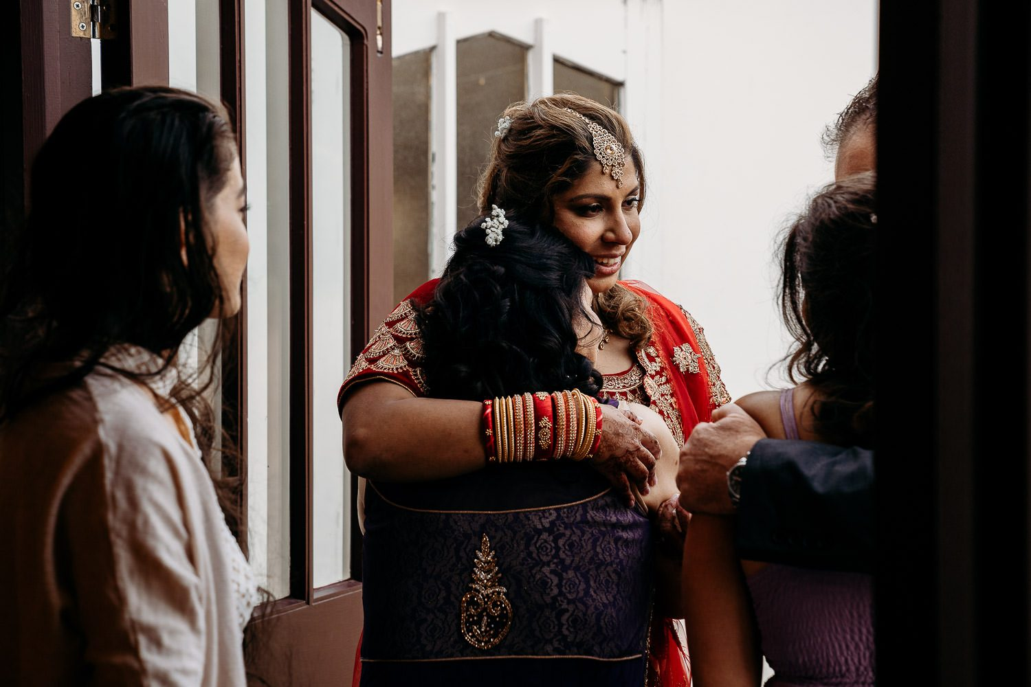 indian bride and mother hugging at wedding reception