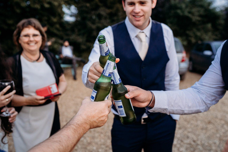 groom and groomsmen cheers with bottled beer