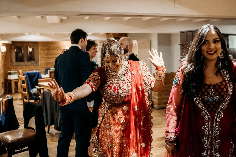 asain bride in red sari dancing