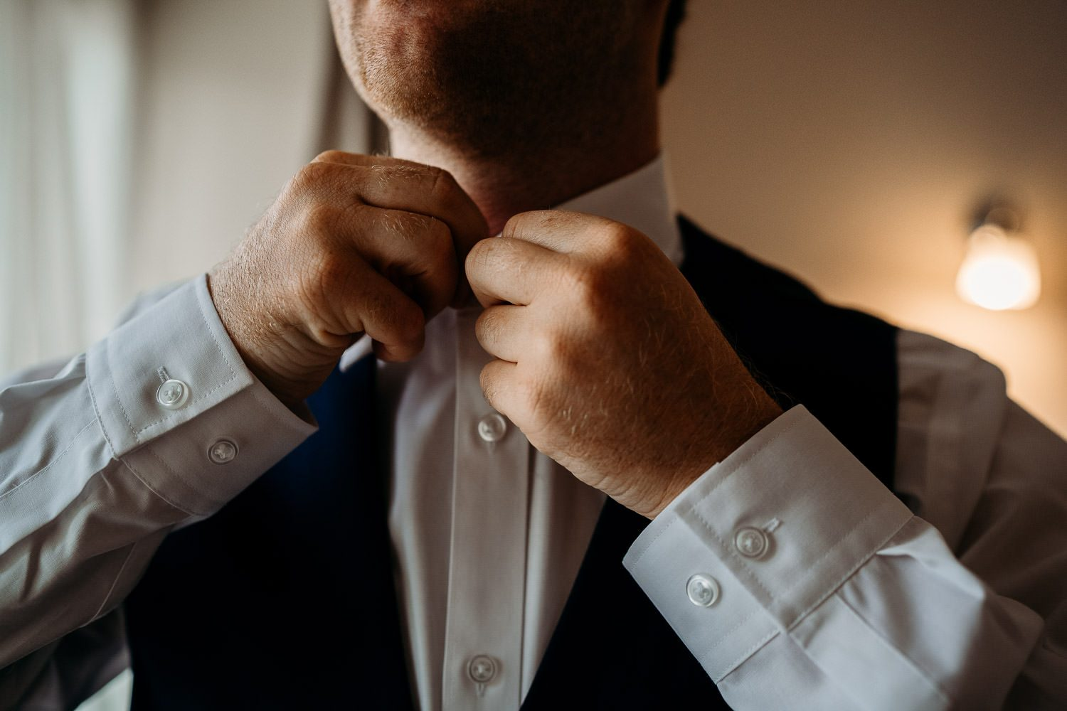 groom doing up his shirt during morning preparations