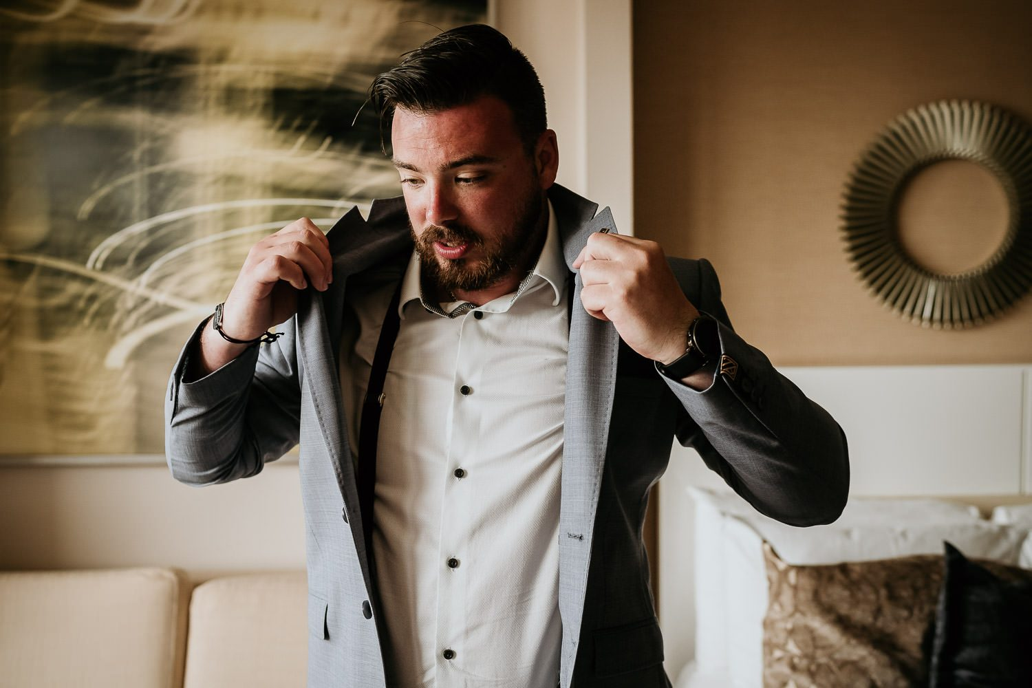 groom putting on suit jacket for wedding
