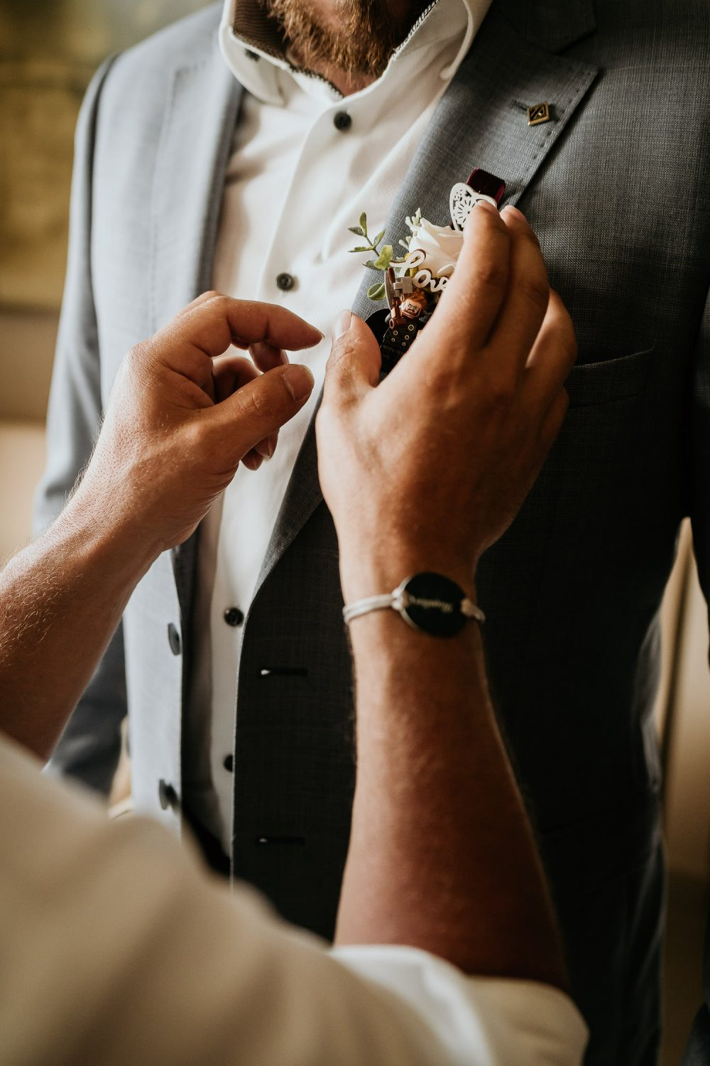 grooms father pinning grooms buttonhole on suit jacket