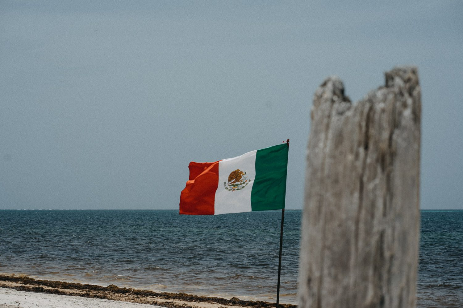 mexican flag blowing in wind on cancun beach
