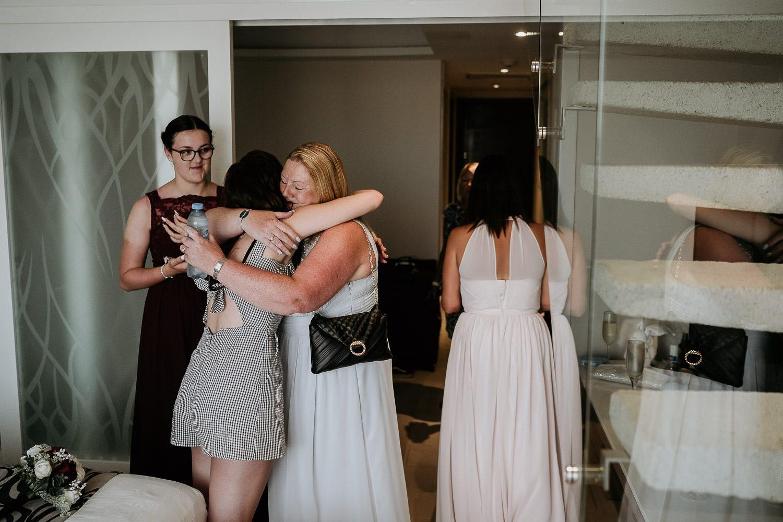 emotional bride hugging mother in law at wedding prep