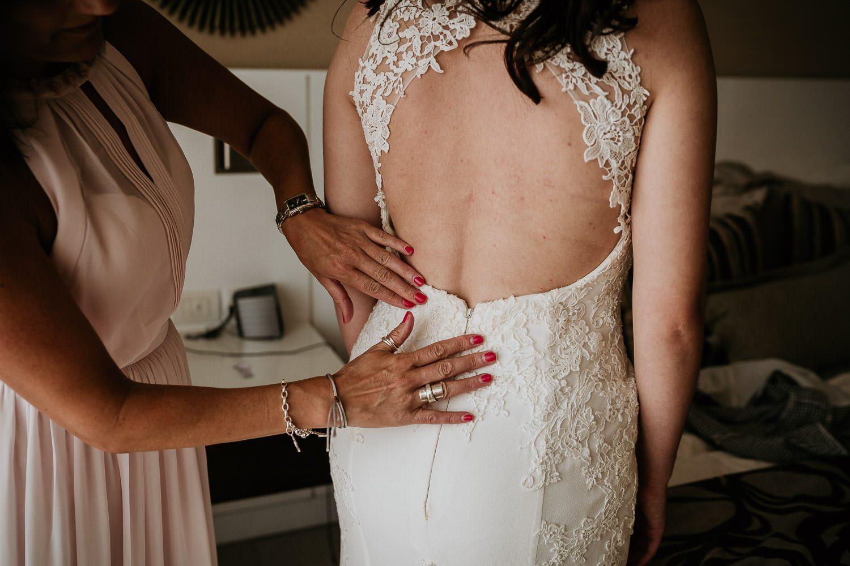 mother of bride adjusting lace on brides wedding dress