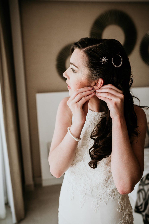 bride putting in earrings before wedding