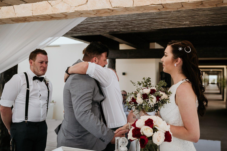 emotional brother of bride hugging groom during destination wedding ceremony