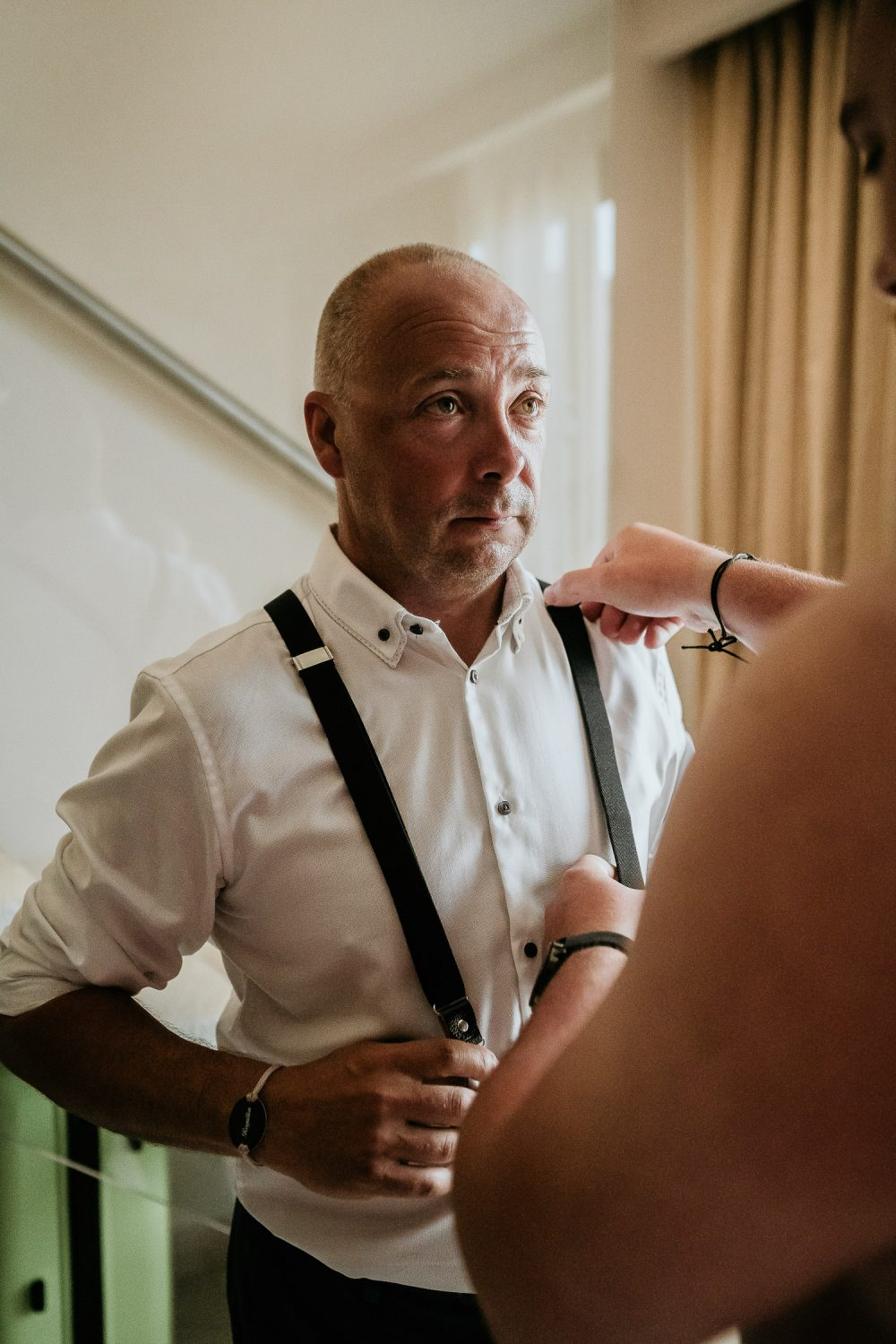 groom helping father of groom with braces for suit