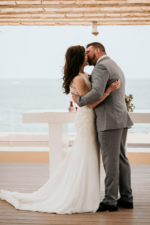bride and groom kissing overlooking royalton riviera