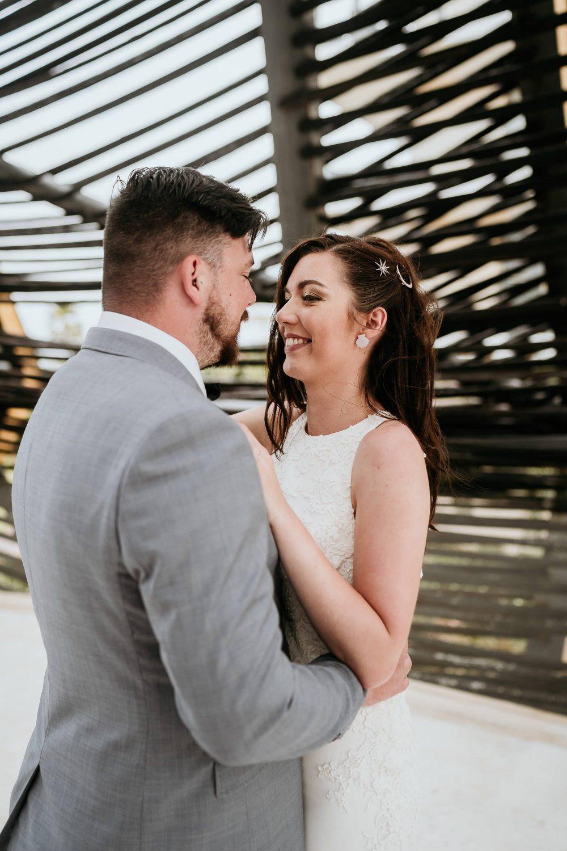 bride and groom cuddling in royalton riviera gazebo