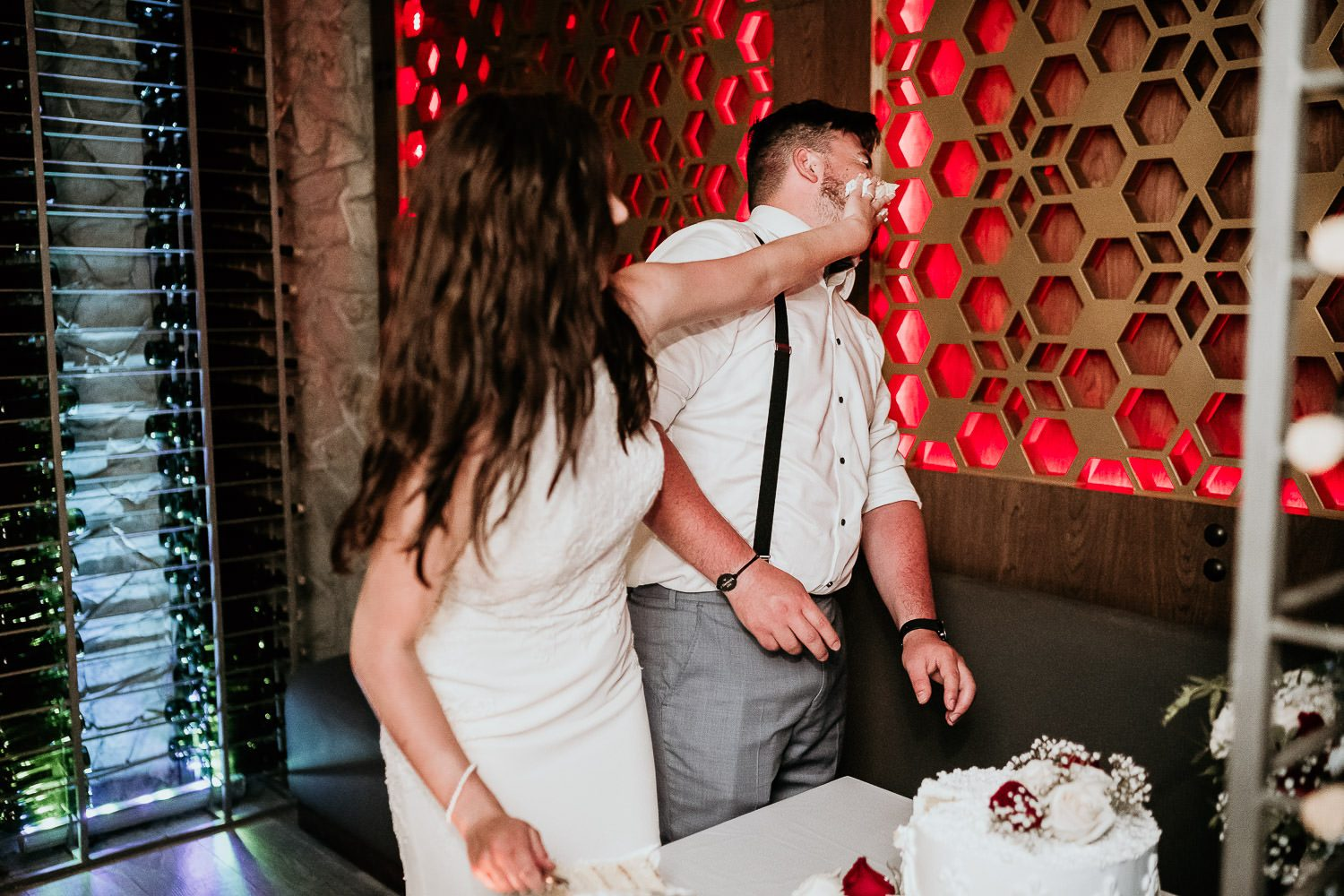 bride putting cake on grooms face in cancun