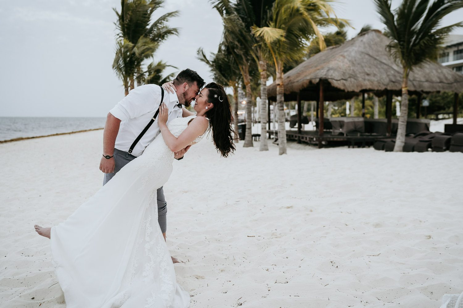 groom kissing bride on beach in cancun