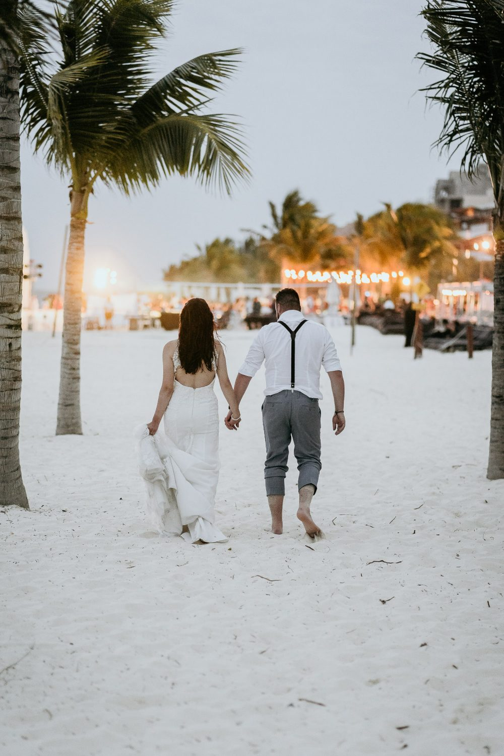 bride and groom walking on mexican beach