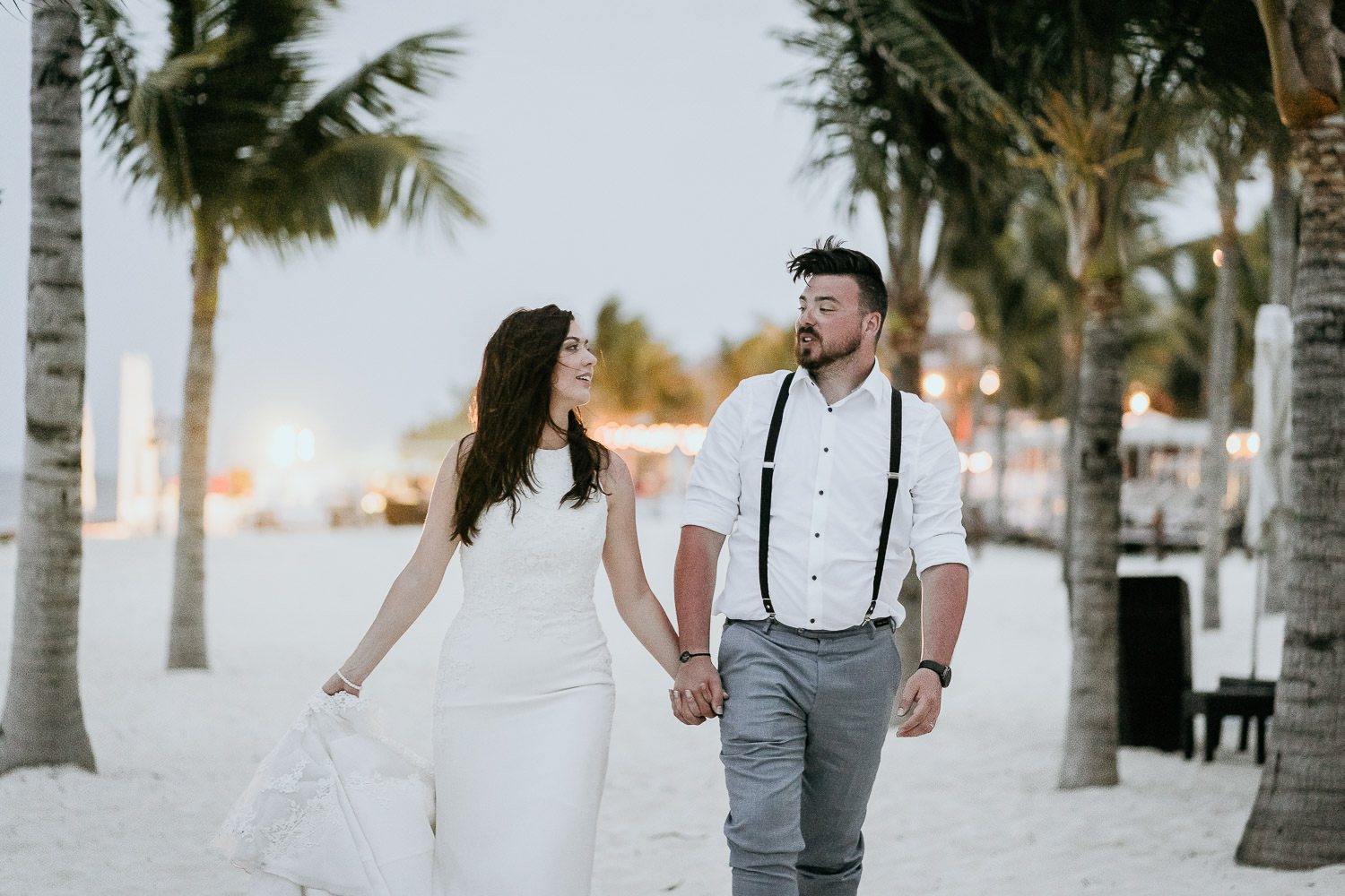 bride and groom walking on beach in cancun