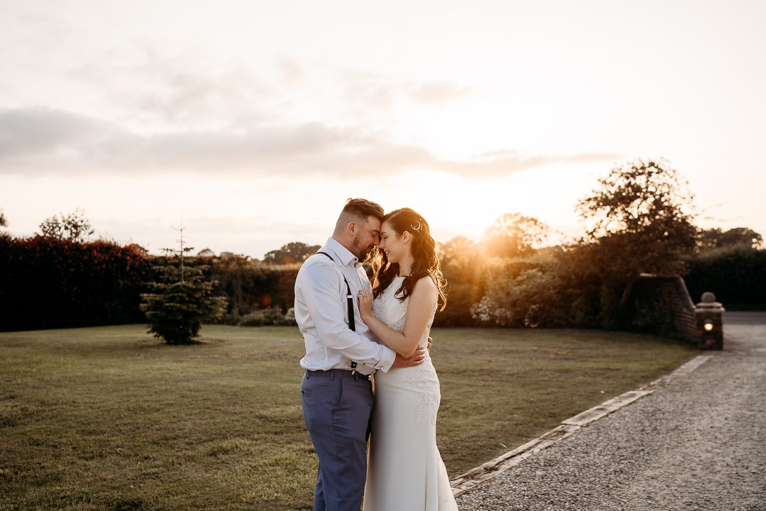 bride and groom holding each other at sunset in garden of blakelands country house