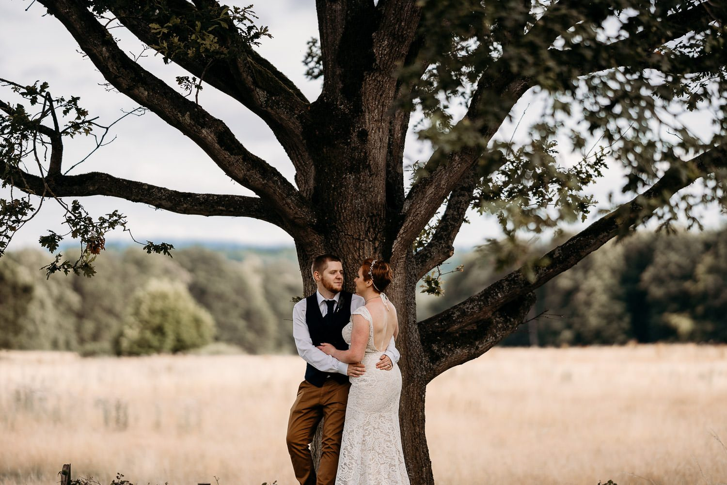 romantic groom leaning on tree and holding bride