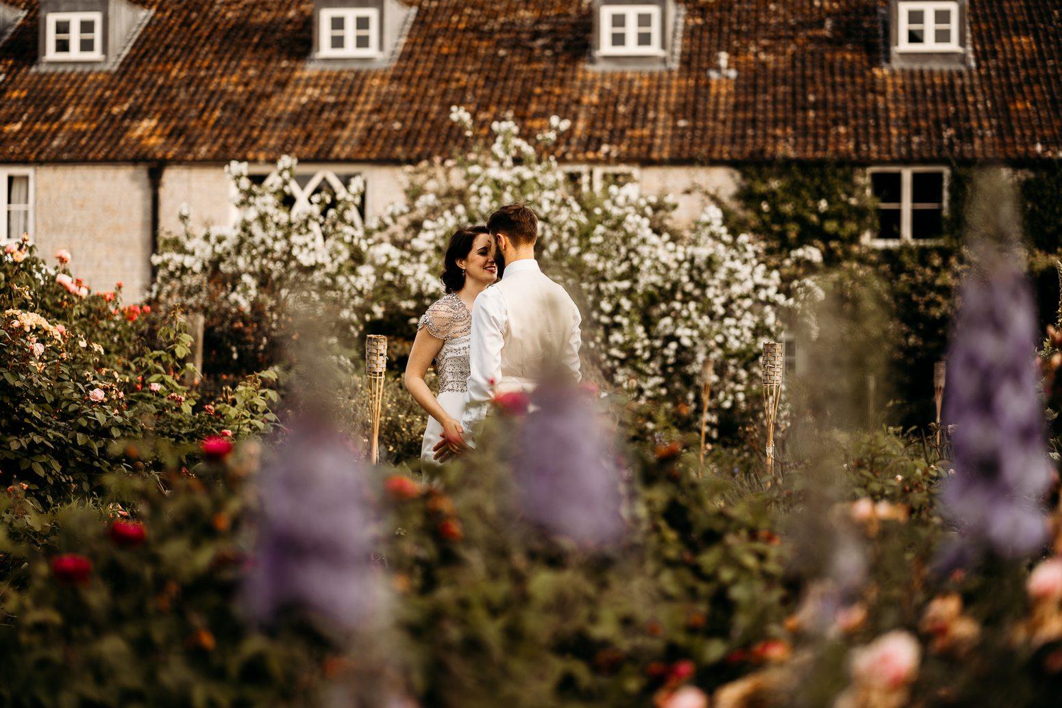 bride and groom in overgrown floral garden