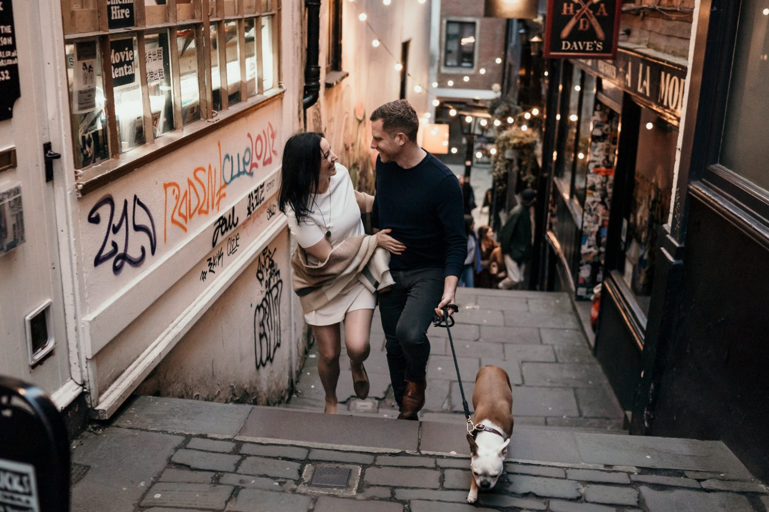 bride, groom and boston terrier walking up christmas steps in bristol